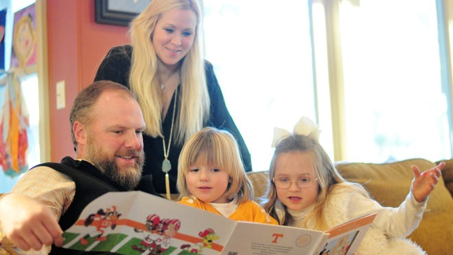 Trey, Ashley, Everett and Lilly Teague (left to right). Trey reads the UT Smokey book to his children