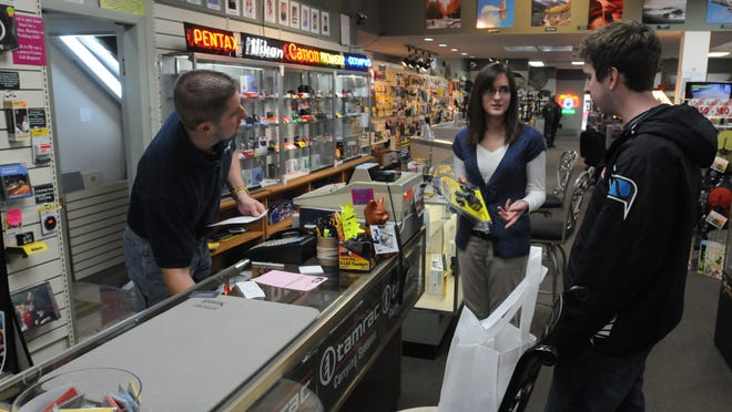 Luke Parmeter purchases video accessories from Andy Ratchman of Camera Casino while Ashley Klatkiewicz talks about a video hood for Parmeter's camera. Camera Casino has been an anchor store in downtown Oshkosh since 1973.