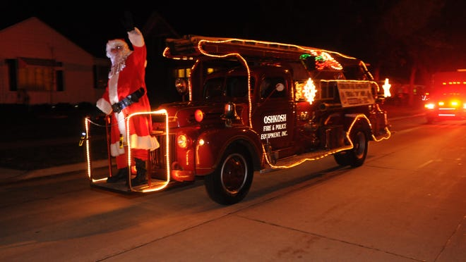 Santa Claus makes the rounds on an antique fire truck as part of the Oshkosh Fire Department's annual holiday Food and Toy Drive in this December 2013