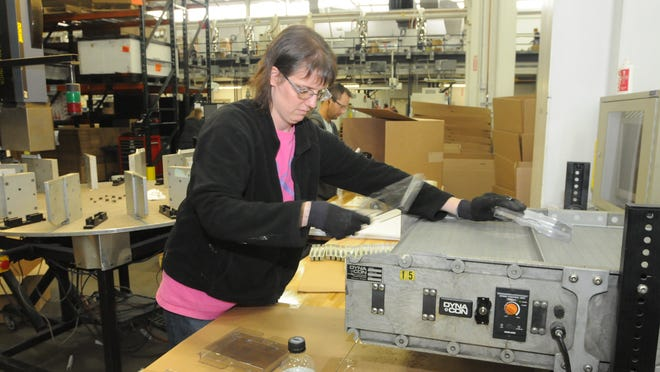 Laurie Bigelow takes the anti-theft DVD cases off the production line to be assembled after the cases were injection molded at EVCO in Oshkosh, Wisconsin.