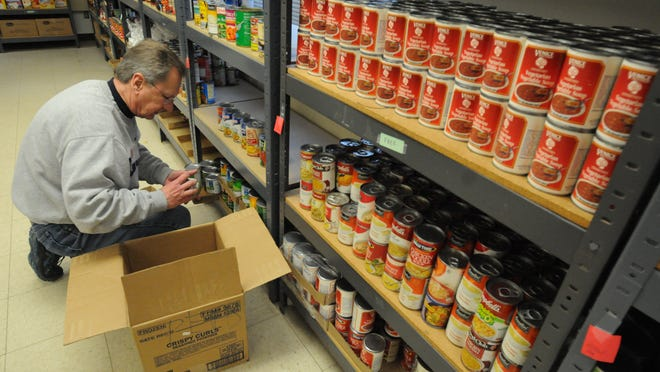 Oshkosh Salvation Army volunteer Ed Wilusz stocks the shelves in the food pantry in 2015.