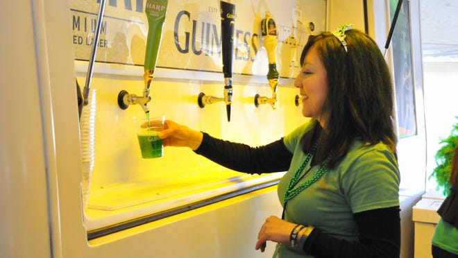 McCarthy's employee Stella Lopez pours green beer during the restaurant and pub's 10th anniversary and St. Patrick's Day tent event in downtown Port Clinton.