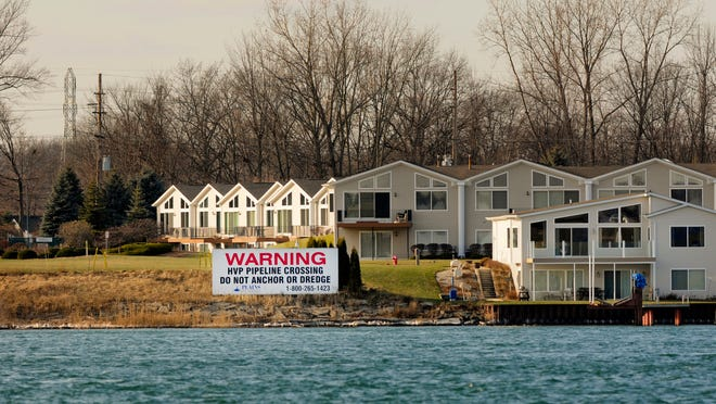 A sign on the shore of the St. Clair River in Marysville warns boaters of pipelines under the St. Clair River Friday as seen from Corunna, Ontario.