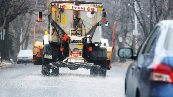 A City of Poughkeepsie truck spreads salt on the roadway . A study found that sodium and chloride concentrations in tested well water increased whenever there was more pavement nearby.
