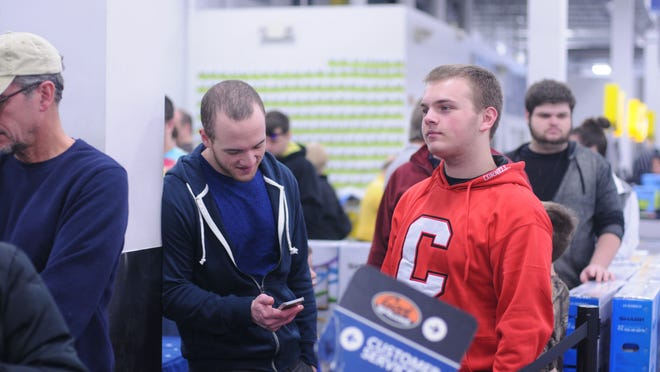 Mitch, left, and Jon Mann wait on line at Best Buy in the Poughkeepsie Galleria to return video games.