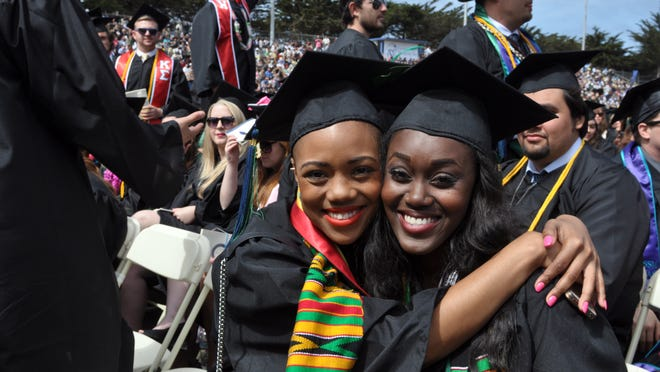 Mojola Osifeso, left, and Lauren Floyd pose for a photo at the 18th CSUMB graduation ceremonies at Freeman Stadium. The university conferred degrees on 1,447 graduates in 2014.