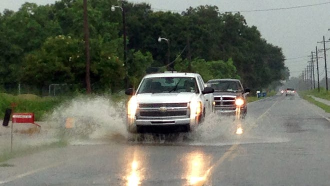 Motorists drive through high water on Chemin Agreable Road in Youngsville during heavy rain showers Friday, July 18, 2014.
