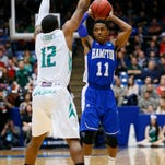 Hampton guard Deron Powers (11) looks to pass while guarded by Manhattan guard RaShawn Stores during the second half on Tuesday in Dayton, Ohio.
