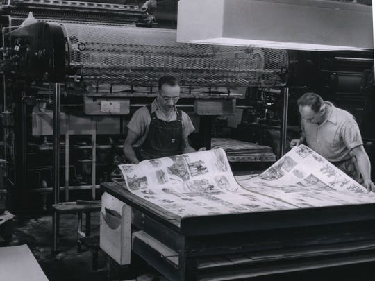 Color registration on work produced from a four color offset press is examined by employees  Leon Kwiecinski (left) and Don Mortenson at  Western Publishing Company in Racine.