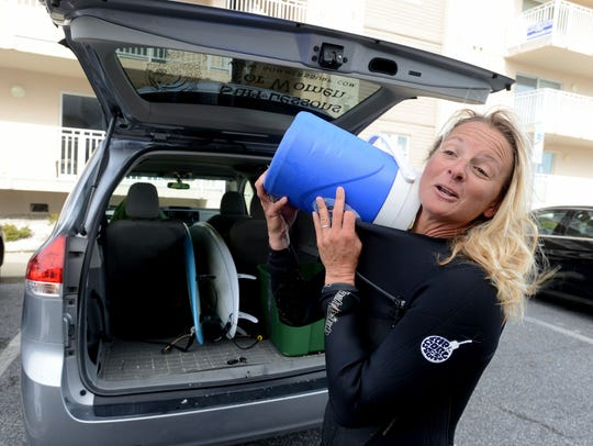 Surf instructor Michelle Sommers pours warm water on