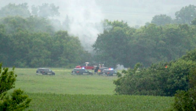 Smoke billows from the scene of a plane crash as emergency vehicles respond in Green County on Sunday. All four people aboard a light aircraft died Sunday after the plane crashed into a wooded area.