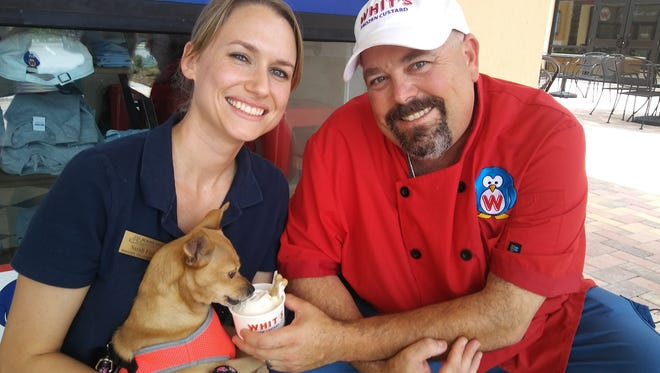 Sarah Fisher, the Humane Society's volunteer program manager and mobile adoption coordinator, and Chris Mass, who owns Whit's of Stuart, give Bella her first sundae.