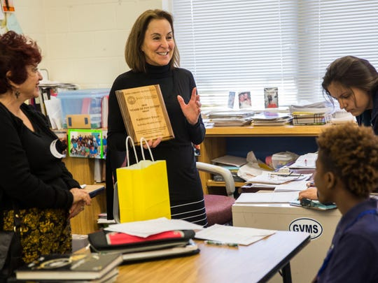 Grandview Middle School eighth-grade teacher Kathleen Deye, center, shows her class the plaque she received Thursday, March 8, 2018, for an Honorable Mention in the Stand Up for Justice Awards.