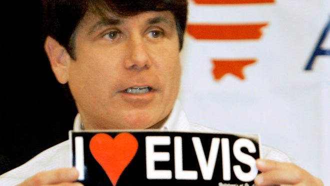 "Former Illinois governor Rod Blagojevich holds an ""I Love Elvis"" bumper sticker at the Illinois Democratic County Chairmen's Association meeting in Springfield, Ill., in 2007."