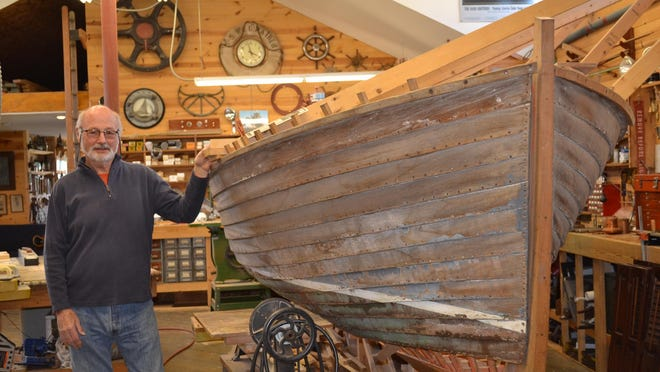 Bill Moon stands next to the 1937 Lyman he is painstakingly restoring in his workshop. Once finished, the boat will look like it just left the factory.