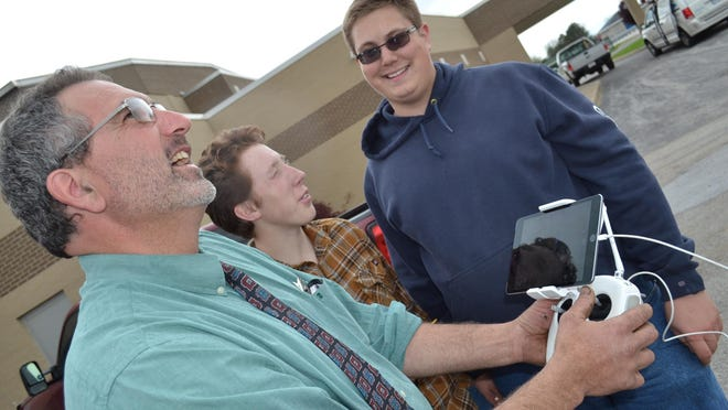 Agriculture education instructor Barrett Zimmerman eyes the ag department's drone flying overhead at Clyde High School. With him are Robert Selvey, center, and Austin Nasser. The ag program uses technology to prepare the students for a variety of fields in agriculture.