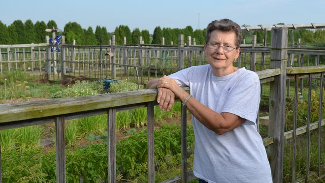 Linda Lambert stands next to the backyard gardens at Bella Cuisine, where much of the produce for her cooking classes are grown. Classes sometimes include tours of the gardens and orchard.