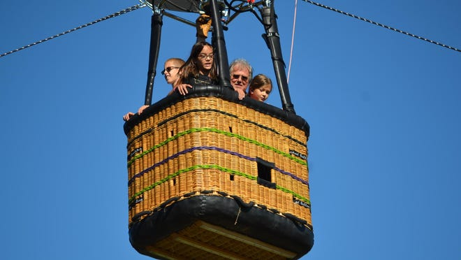 Ed Benlein gave a free ride in his hot air balloon to, from left, Zach Conklin, Allie Randolph, and Braylee Laughin at Fremont Baptist Temple.
