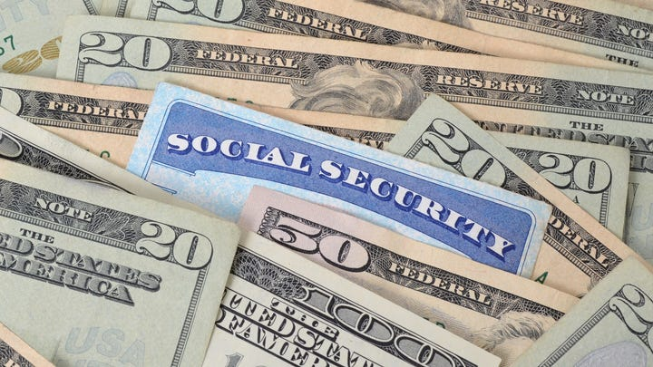 Social Security card embedded in spread-out money.