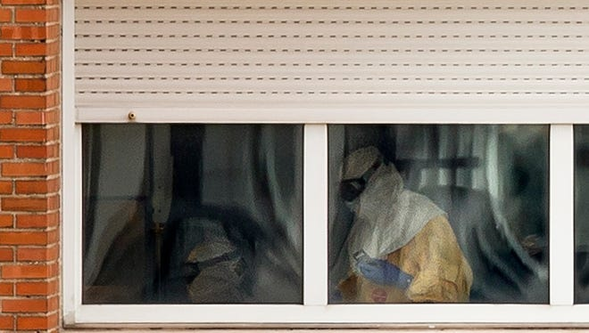 Medical practitioners wearing protective clothing are seen attending a patient inside an isolated ward on the sixth floor of the the Carlos III hospital in Madrid, Spain.
