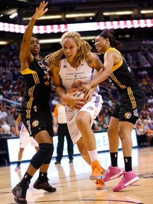 Phoenix Mercury center Brittney Griner splits the defense by Tulsa Shock forwards Vicki Baugh, left, and Plenette Pierson during the second quarter