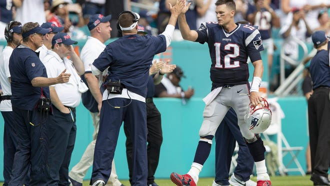 New England Patriots quarterback Tom Brady receives a high five after completing touchdown pass against the Dolphins during a game this past season.