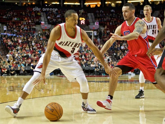 Portland Trail Blazers guard C.J. McCollum, left, dribbles around Los Angeles Clippers guard J.J. Redick during the first half of an NBA basketball game in Portland, Ore., Friday, Nov. 20, 2015.