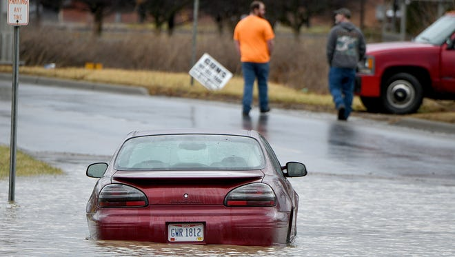 An abandoned car sits deep in water Thursday on North Diamond Street after heavy rains Wednesday night and Thursday morning flooded some of the main routes around downtown Mansfield.