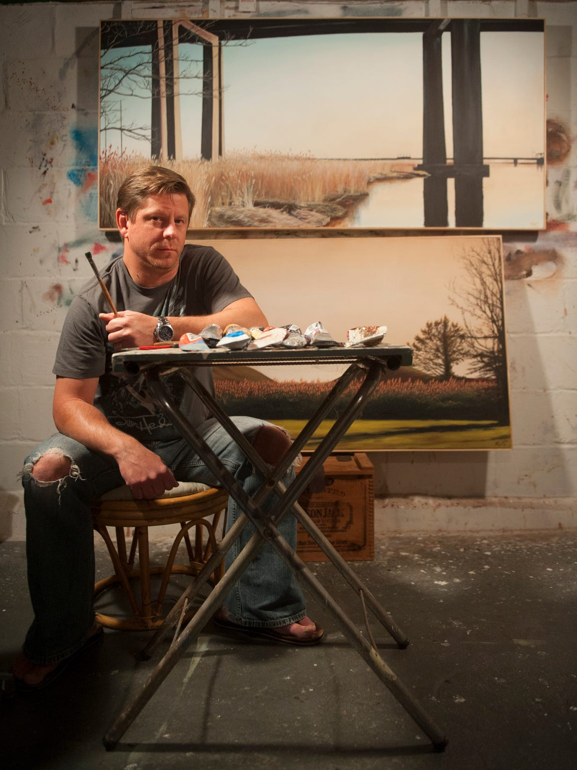 """Painter Matthew Green sits by some of his work in the studio of his Oaklyn home.  . """"There's a slow, smoldering passion in things that are rusting and decaying. To me, they're very powerful. I wanted to share that feeling with people. As a society, we are throwing away these entire structures … that to me seems kind of crazy."""""""