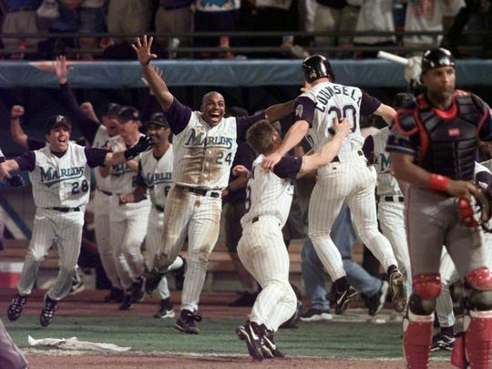 Florida Marlins' Craig Counsell (30) is greeted by teammates, including Bobby Bonilla (24) and John Cangelosi (28), after he scored the winning run on an Edgar Renteria hit in Game 7 of the World Series early Monday, Oct. 27, 1997, at Miami's Pro Player Stadium.
