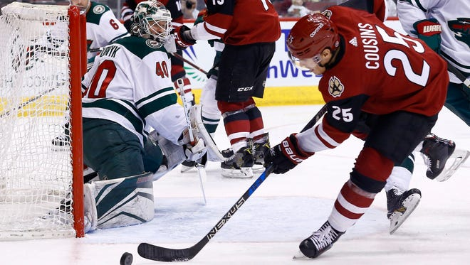 Arizona Coyotes center Nick Cousins (25) is unable to control the puck in front of Minnesota Wild goaltender Devan Dubnyk (40) during the second period of an NHL hockey game Saturday, March 17, 2018, in Glendale, Ariz. The Wild won 3-1.