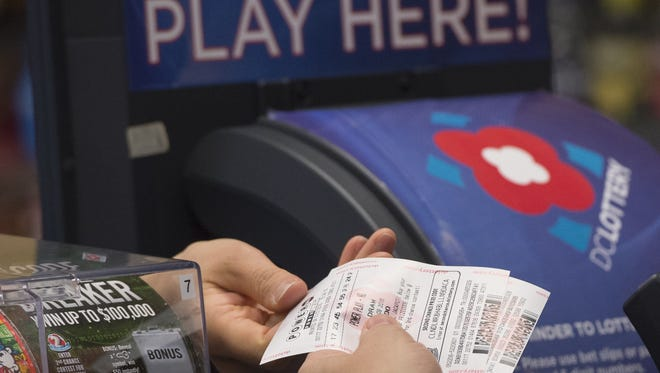 A man purchases a Powerball lottery ticket at a convenience store in Washington, DC, on January 7, 2016.