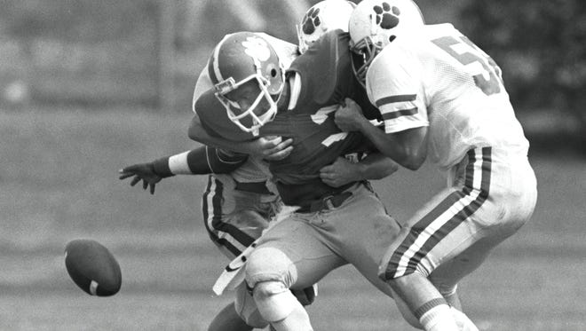 October 12, 1985 - Rhodes College halfback Don Duggan struggles to break free of David Folds and Rob McIntosh of the University of the South at Sewanee to recover his own fumble. Sewanee covered the loose ball, but Duggan later scored on a 7-yard run and the Lynx won 20 to 7. The victory, before a homecoming crowd of 3,000 at Fargason Field, upped Rhodes' record to 5 and 1.
