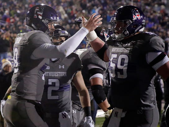 Northwestern quarterback Clayton Thorson, left, celebrates with offensive line J.B. Butler after scoring a touchdown during the first half of an NCAA college football game against Purdue, Saturday, Nov. 11, 2017, in Evanston, Ill. (AP Photo/Nam Y. Huh)