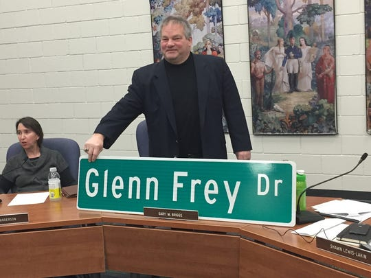 Gary Briggs, president of the Royal Oak School Board, poses with the Glenn Frey Drive sign after successful renaming vote Thursday night.