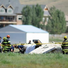 Police and firefighters work on the scene where three people were killed and two others injured after an airplane crashed in a field northwest of the main runway at Erie Municipal Airport while coming in for a landing in Erie, Colo., Sunday, Aug. 31, 2014.