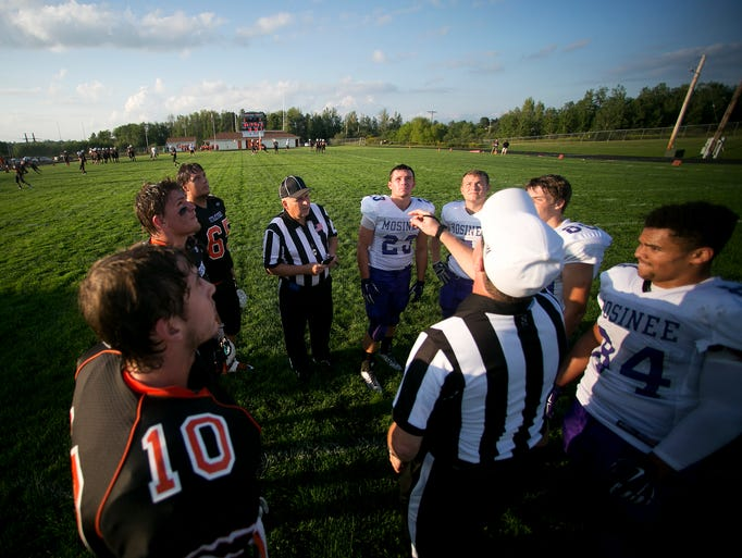 Captains of the Stratford and Mosinee football teams meet at the center of the field for the coin flip before the non-conference football game at Tiger Stadium in Stratford, Friday, Aug. 22, 2014.