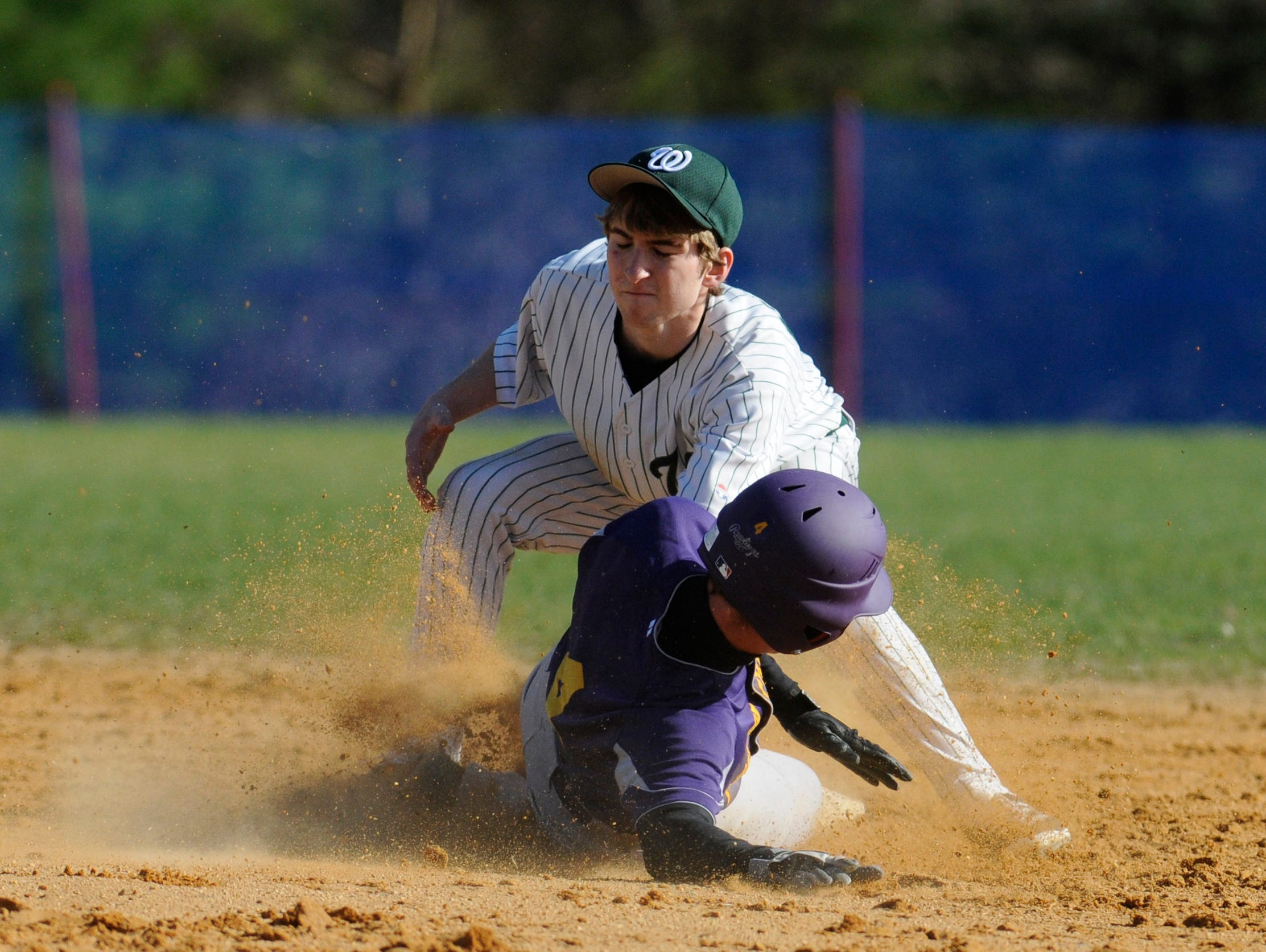 Rhinebeck's Chris Cassens slides into second base under Webutuck's Chris Milano during Wednesday's game at Rhinebeck.