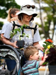 Stephanie and Hayden Otkin look at flowers  Saturday May 13, 2017, during the opening weekend of the Downtown Fond du Lac Farmers Market. Doug Raflik/USA TODAY NETWORK-Wisconsin