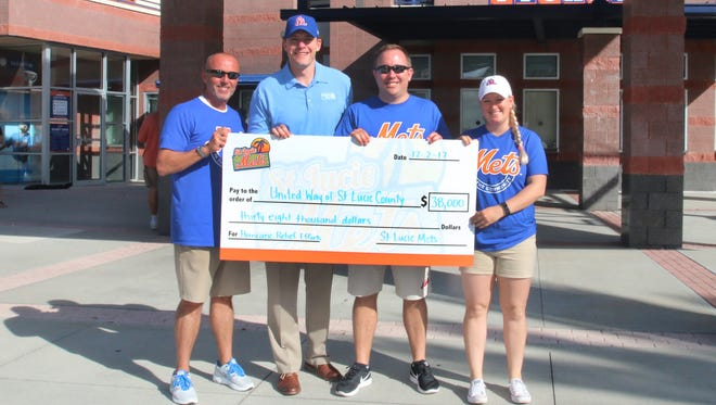 Mets General Manager of Florida Operations Paul Taglieri, left, presents a check to Mustard Seed Ministries Director Pastor Todd Smith, with assistance from Mets staffers Traer Van Allen and Kasey Blair.