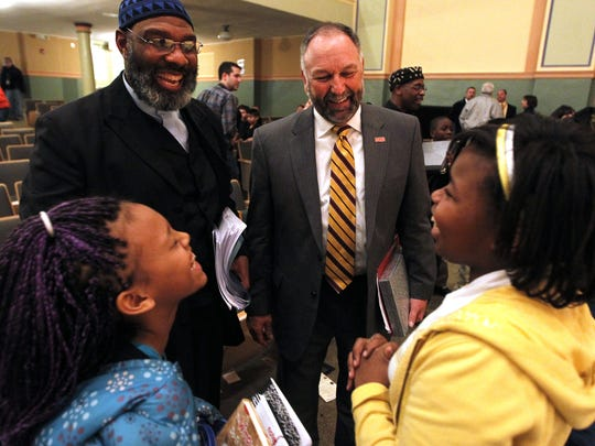 Steven Leath, President of Iowa State University, back right, with Iowa representative Ako Abdul-Samad, visits with King elementary fifth graders Nehya Yann, left, and Angel Lewis during a ceremony recognizing the legacy of Dr. Martin Luther King Jr. in January 2013 in Des Moines.