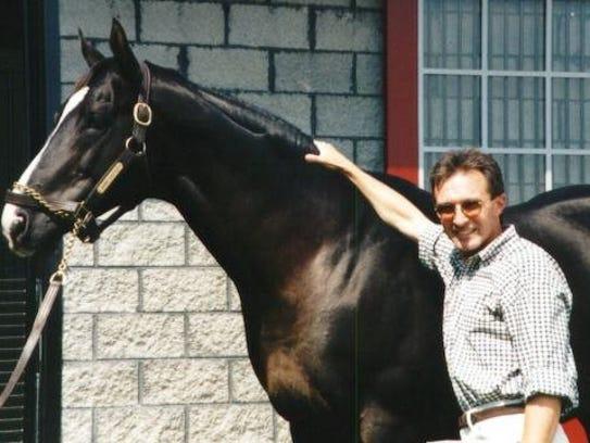 Clint Goodrich stands with Saint Ballado, a colt he