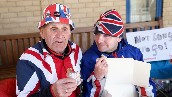 Royal fans Terry Hutt and John Loughrey enjoy pastries sent by Prince William and Duchess Kate as they wait outside St. Mary's Hospital in London on April 28.