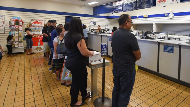 Customers line up for postal transactions at the United States Post Office in Barrigada on Nov. 20, 2017.