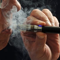 In this photo illustration, a smoker puffs on an e-cigarette. E-cigarettes are being touted as a safe alternative to traditional lighted tobacco products. Studies are looking at the chemical makeup of the secondhand vapor which is breathed out like smoke.