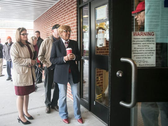 Jackson K-8 Polling Clerk Wayne Wilson, right, of York City, opens the door right at 7 a.m., as Carol Hill-Evans, middle, Lynn and Susan Adams, left and others await their turn to vote Tuesday, Nov. 8, 2016. Amanda J. Cain photo