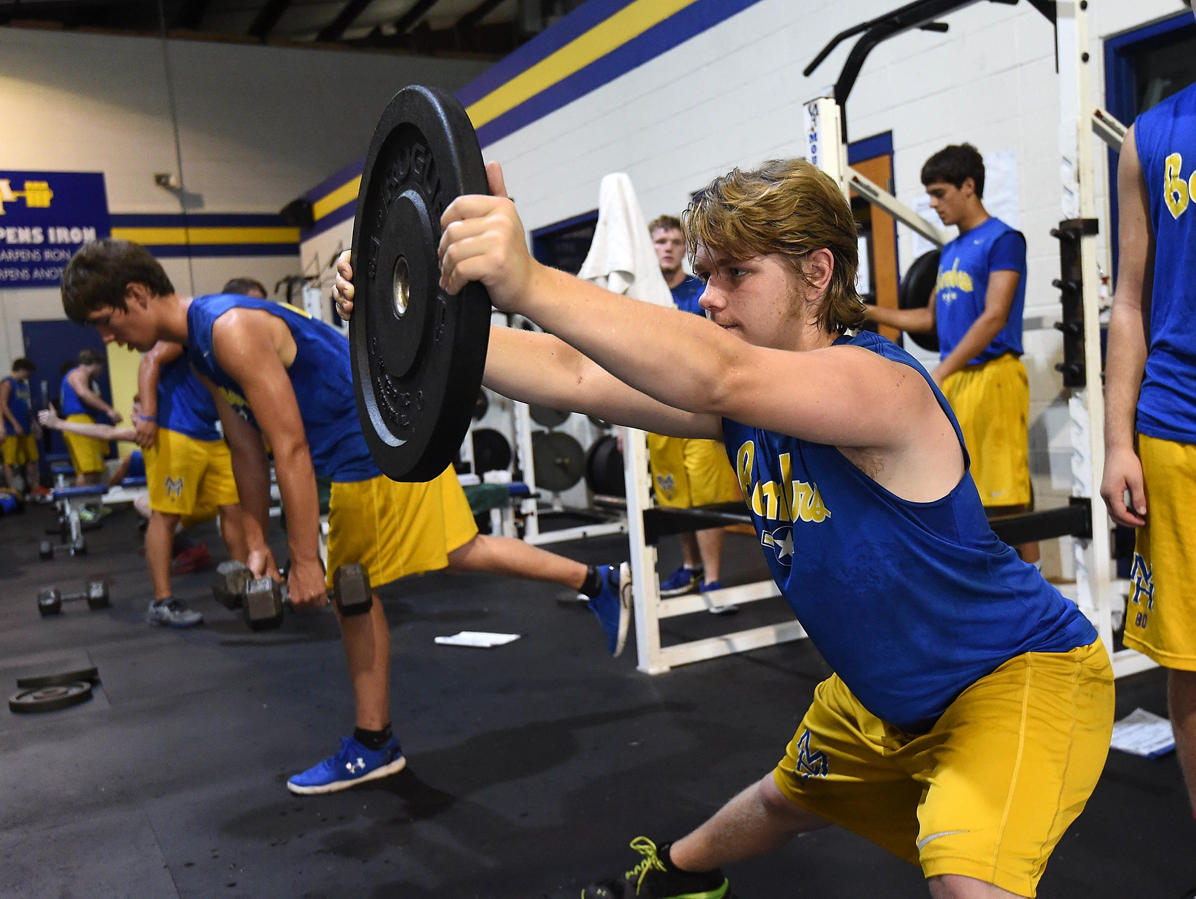 Bomber football player Jesse Dunn lifts weights Tuesday during a voluntary team practice.