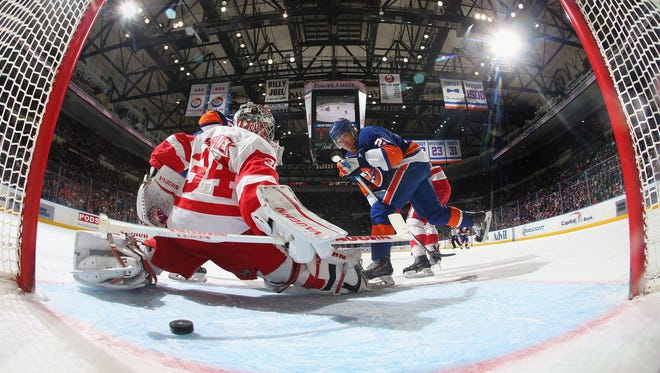 Kyle Okposo #21 of the New York Islanders scores a powerplay goal at 9:02 of the first period against Petr Mrazek #34 of the Detroit Red Wings at the Nassau Veterans Memorial Coliseum on March 29, 2015 in Uniondale, New York.
