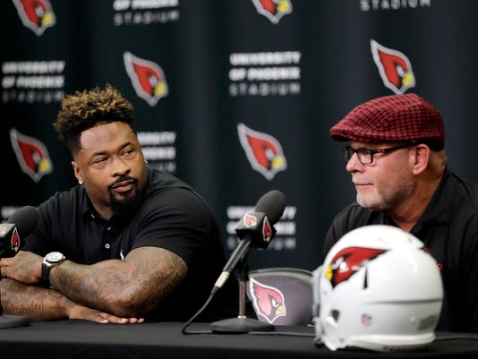 Darnell Dockett jokingly glares as he blames head coach Bruce Arians, right, for preventing Dockett from winning a Super Bowl in 2008 after signing a contract with the Arizona Cardinals, Monday, July 25, 2016, in Tempe, Ariz. Dockett, who spent 11 seasons in Arizona, signed a one-day contract so he could retire as a Cardinal. (AP Photo/Matt York)