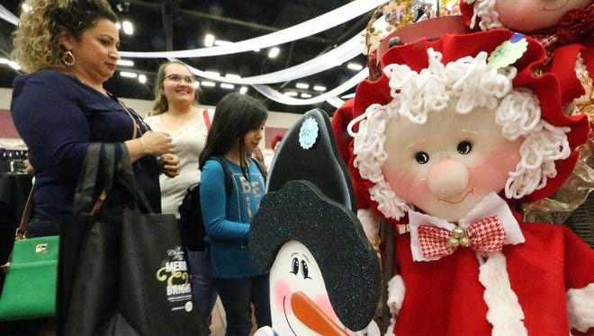 Marie Terrazas, left, looks at Christmas-themed items for sale with daughter Zoey Terrazas, 8, on Friday at the Junior League of El Paso's A Christmas Fair.